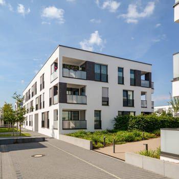 modernes-mehrfamilienhaus-gehweg-mit-gruenanlage-350px